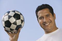 Esfera de futebol da terra arrendada do homem Fotografia de Stock