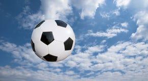 Esfera de futebol e cloudscape fotografia de stock