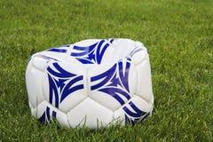 Esfera de futebol horizontalmente branca e azul na grama Foto de Stock Royalty Free