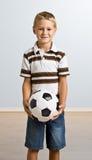 Esfera de futebol nova da terra arrendada do menino Fotos de Stock Royalty Free