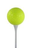 Esfera de golfe amarela isolada em um T branco Fotos de Stock Royalty Free