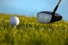 Esfera de golfe aproximadamente a ser golpeada pelo excitador com grama Imagem de Stock Royalty Free