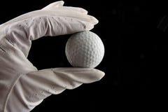 Esfera de golfe da terra arrendada da mão imagens de stock royalty free