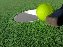 Esfera de golfe diminuto perto do furo Fotografia de Stock