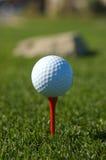 Esfera de golfe em um T vermelho Imagem de Stock Royalty Free