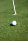 Esfera de golfe em um verde de colocação Imagens de Stock
