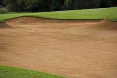 Esfera de golfe na armadilha de areia imagem de stock