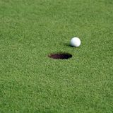 Esfera de golfe na frente do furo Foto de Stock Royalty Free
