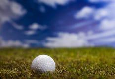 Esfera de golfe na grama verde sobre um céu azul Fotos de Stock Royalty Free