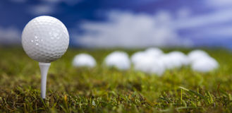 Esfera de golfe na grama verde sobre um céu azul Foto de Stock Royalty Free