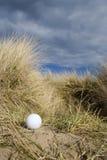 Esfera de golfe nas dunas Foto de Stock