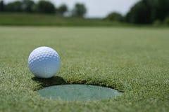 Esfera de golfe no copo com fairway Foto de Stock Royalty Free