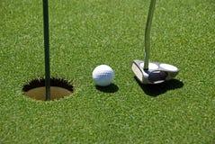 Esfera de golfe no furo da prática Imagens de Stock Royalty Free