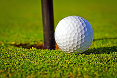 Esfera de golfe perto do furo Imagens de Stock Royalty Free
