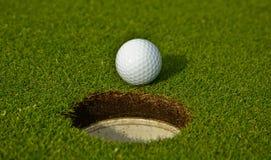 Esfera de golfe perto do furo foto de stock royalty free