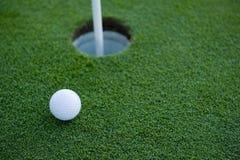 Esfera de golfe perto do furo fotografia de stock