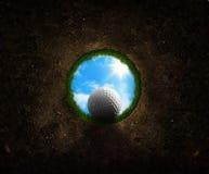 Esfera de golfe que cai no copo Fotografia de Stock