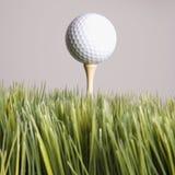 Esfera de golfe que descansa no T na grama. Foto de Stock Royalty Free