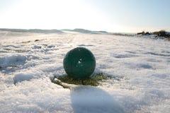 A esfera de golfe verde na neve cobriu o campo de golfe Foto de Stock Royalty Free