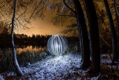 A esfera de incandescência em um fundo de um inverno bonito ajardina Foto de Stock