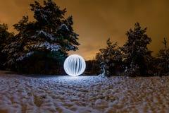A esfera de incandescência em um fundo de um inverno bonito ajardina Imagens de Stock
