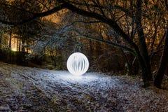 A esfera de incandescência em um fundo de um inverno bonito ajardina Foto de Stock Royalty Free