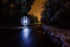 A esfera de incandescência em um fundo de um inverno bonito ajardina Imagens de Stock Royalty Free