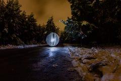 A esfera de incandescência em um fundo de um inverno bonito ajardina Fotos de Stock