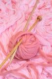 Esfera de lanas rosadas con las agujas Fotos de archivo