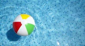 Esfera de praia que flutua na piscina foto de stock