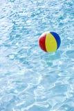 Esfera de praia que flutua na superfície da piscina Foto de Stock Royalty Free