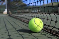 A esfera de tênis encontra-se ao lado de uma rede na corte Fotografia de Stock