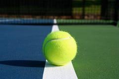 Esfera de tênis na corte com rede no fundo Imagem de Stock