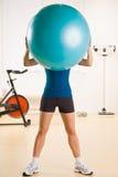 Esfera do exercício da terra arrendada da mulher no clube de saúde Fotografia de Stock
