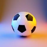esfera do futebol ou de futebol com luz da cor Fotografia de Stock Royalty Free