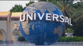 Esfera do mundo de Universal Studios em Citywalk e palmeiras na área de Universal Studios filme