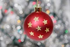 Esfera dourada vermelha do Natal de encontro ao fundo prateado Imagens de Stock