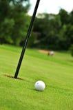 Esfera e furo de golfe fotografia de stock