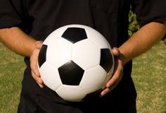 Esfera e mãos de futebol foto de stock