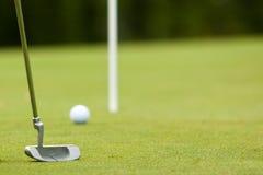 Esfera e putter de golfe perto do verde e da bandeira Imagem de Stock Royalty Free