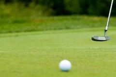 Esfera e putter de golfe perto do verde e da bandeira Fotografia de Stock Royalty Free