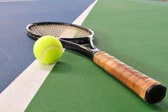 A esfera e a raquete de tênis em uma corte alinham fotografia de stock royalty free