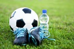 Esfera e sapatas de futebol Foto de Stock