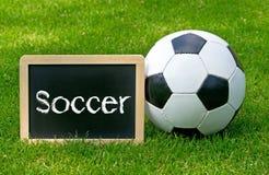 Esfera e sinal de futebol na grama Fotografia de Stock