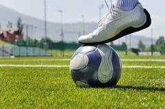 Esfera humana do pé e de futebol Fotografia de Stock