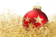 Esfera maçante vermelha do Natal no algodão dourado do glitter Foto de Stock Royalty Free