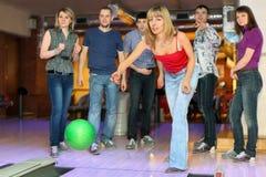 A esfera para o bowling, amigos do throw da menina preocupa-se para ela Imagens de Stock