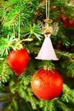 Esfera roja, corazón rojo y ángel del vidrio en el árbol de navidad fotografía de archivo libre de regalías