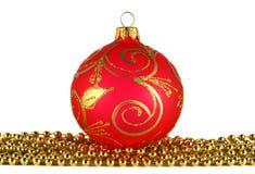 Esfera vermelha do Natal e festão dourada Fotos de Stock Royalty Free