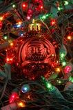 Esfera vermelha do Natal em luzes de Natal Imagens de Stock Royalty Free